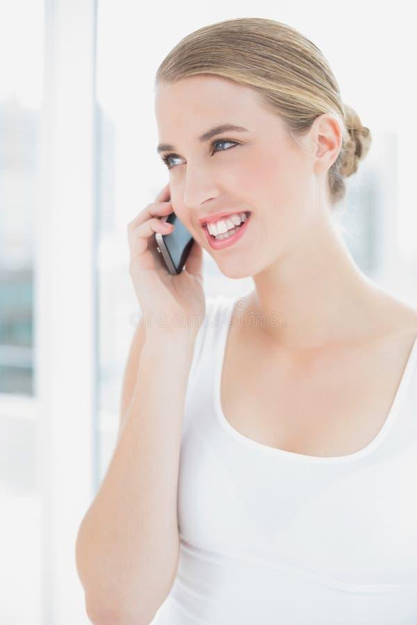 Chiuda su sulla donna sportiva sorridente che ha una telefonata immagine stock