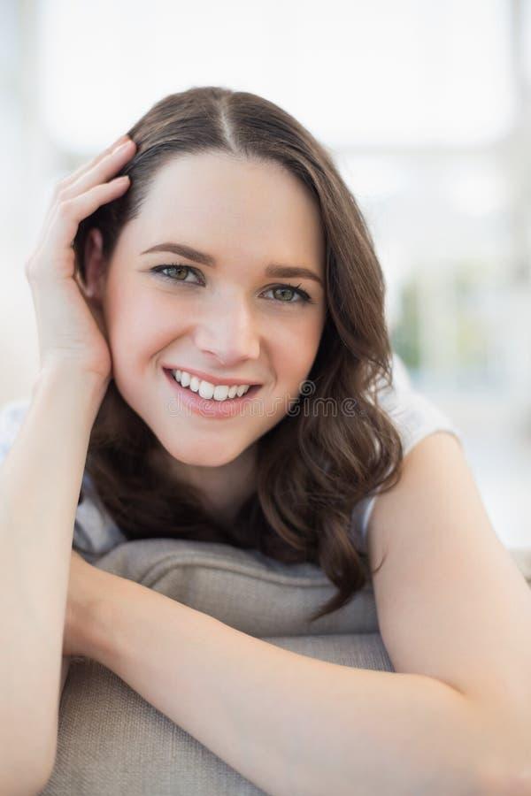 Chiuda su sulla donna sveglia sorridente che si trova su uno strato accogliente immagine stock libera da diritti