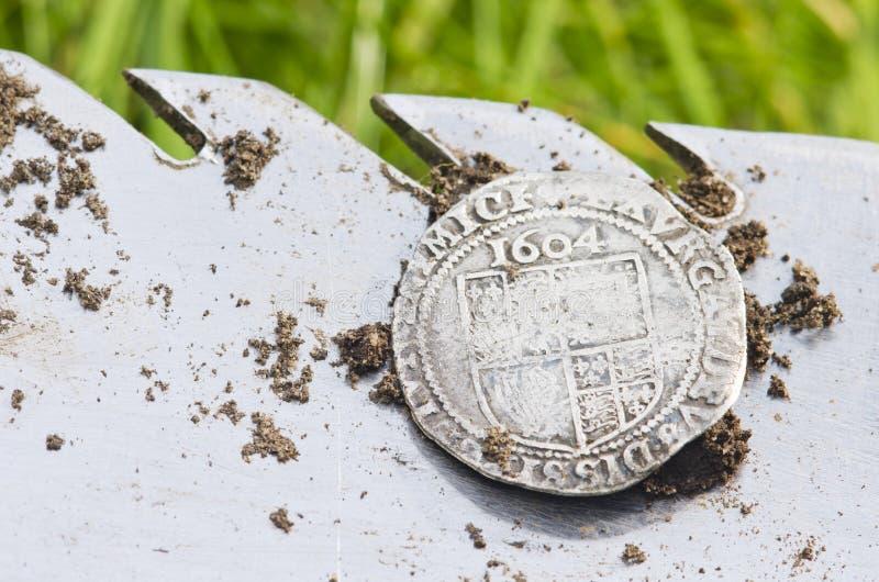Chiuda su sulla vecchia, moneta d'argento martellata esposta su una pala, trovata nella vangata di vita dal metal detector fotografie stock