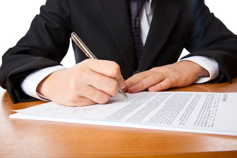 Chiuda in su sulle mani dell'uomo d'affari che firmano un contratto immagine stock libera da diritti