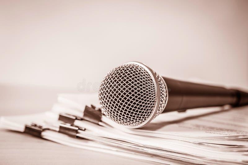 Chiuda su un microfono con il documento cartaceo, concetto dell'altoparlante o immagine stock