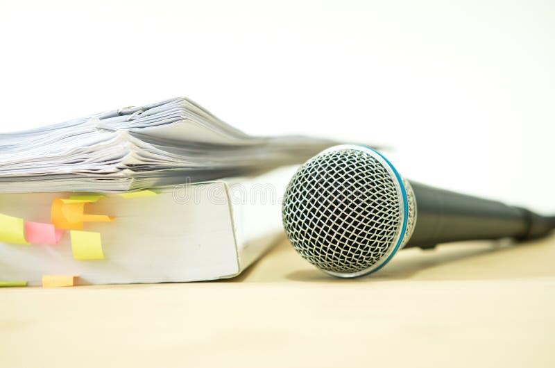 Chiuda su un microfono con il documento cartaceo, concetto dell'altoparlante o fotografia stock