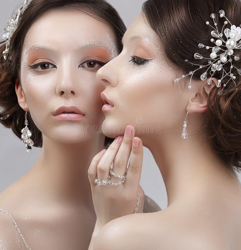 Chiuda su un ritratto di due donne alla moda con trucco d'avanguardia fotografia stock
