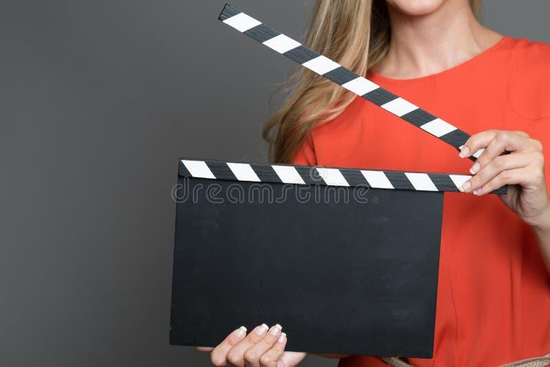Chiuda su una donna bionda che tiene un ciac fotografie stock libere da diritti