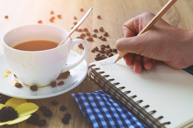 Chiuda su una donna che la mano scrive la lettera di storia ed abbia coff bianco fotografia stock