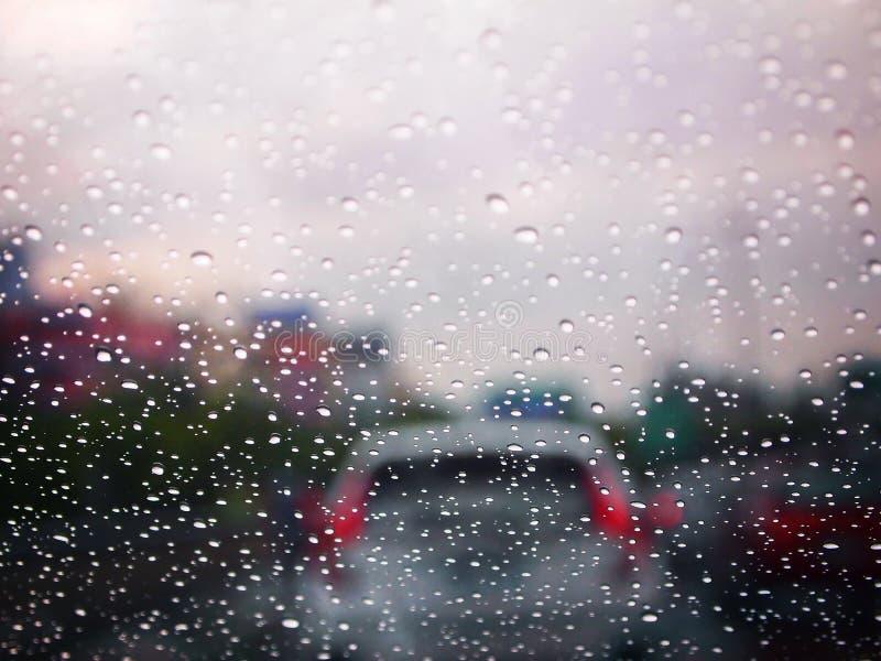 Chiuda su una goccia di acqua di pioggia su un winshield con ingorgo stradale vago su una via, il fuoco selettivo, la struttura a immagine stock