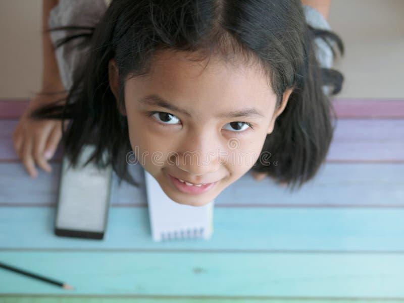 Chiuda su una ragazza asiatica che cerca una macchina fotografica con lo smartphone e un taccuino sulla tavola fotografia stock