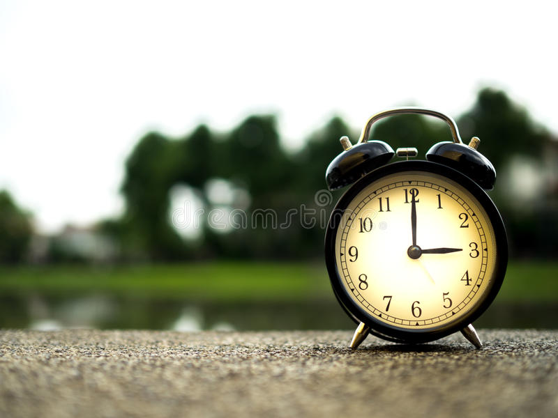 Chiuda su una sveglia con il fondo della natura, concetto di tempo immagini stock