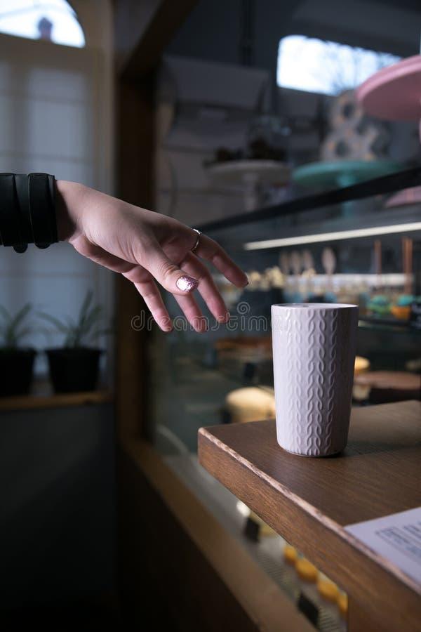 Chiuda su su una tavola di legno marrone sta una tazza bianca fotografia stock libera da diritti