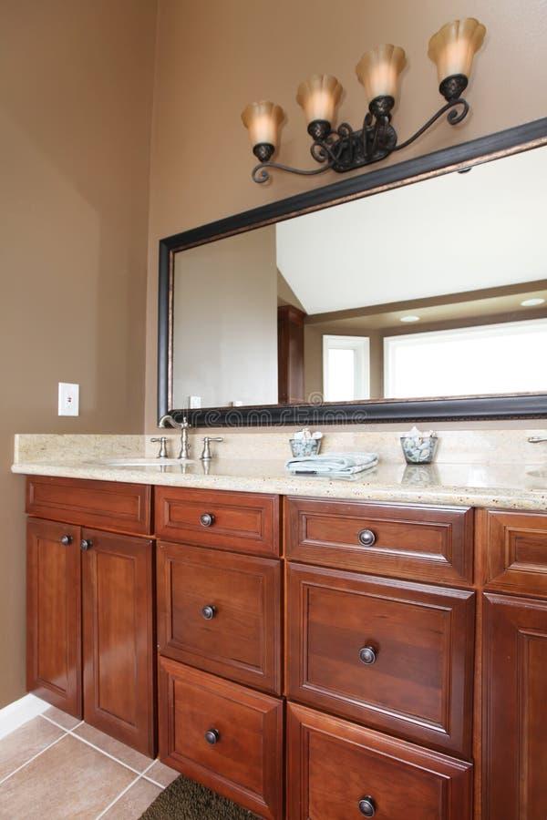 Chiuda sugli armadietti e sullo specchio di stanza da bagno di legno di lusso immagine stock - Armadietti da bagno ...