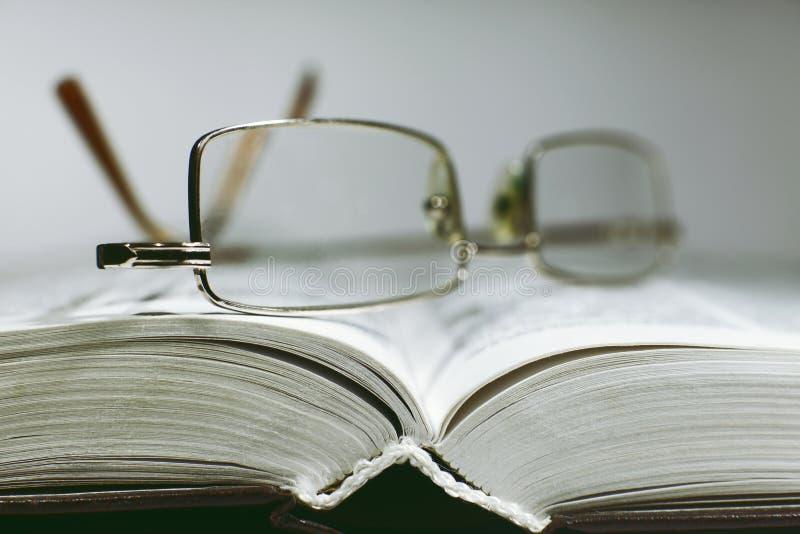 Chiuda sugli occhiali aperti della pagina e della lettura del libro fotografie stock