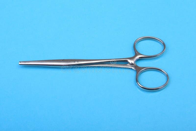 Chiuda sugli strumenti chirurgici e sugli strumenti sul fondo blu dello specchio Fuoco selettivo immagini stock