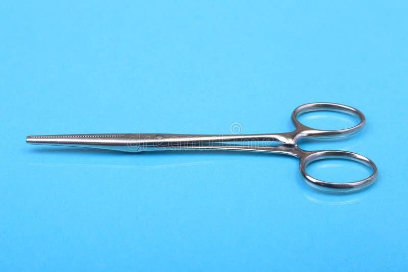 Chiuda sugli strumenti chirurgici e sugli strumenti sul fondo blu dello specchio Fuoco selettivo immagine stock