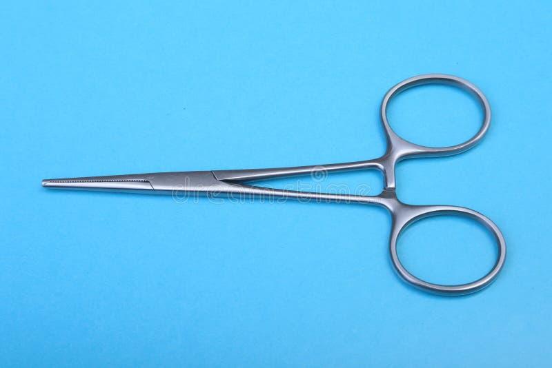 Chiuda sugli strumenti chirurgici e sugli strumenti sul fondo blu dello specchio Fuoco selettivo fotografie stock