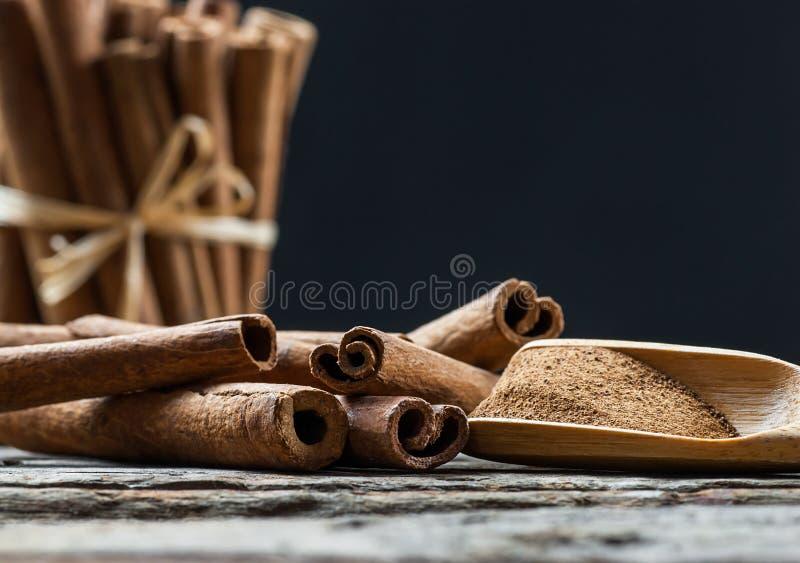 Chiuda sui bastoni di cannella e sulla polvere della cannella in cucchiaio di legno sul fondo di legno della tavola fotografie stock libere da diritti
