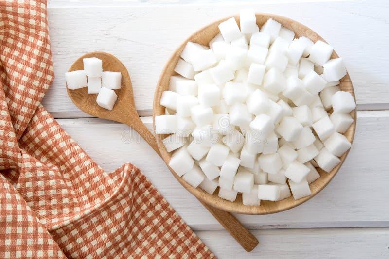 Chiuda sui cubi dello zucchero in ciotola di legno sulla tavola, sulla vista superiore o sul colpo sopraelevato immagine stock