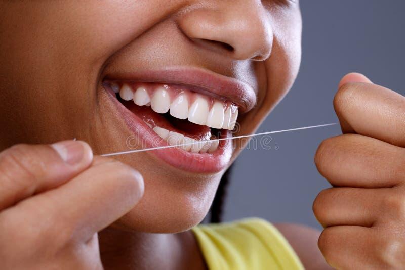 Chiuda sui denti che puliscono facendo uso del filo per i denti immagine stock