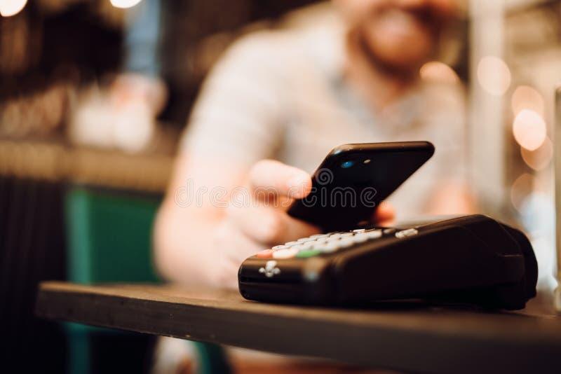 Chiuda sui dettagli del pagamento senza fili, cliente che per mezzo del telefono cellulare, dispositivo con la tecnologia del nfc immagine stock