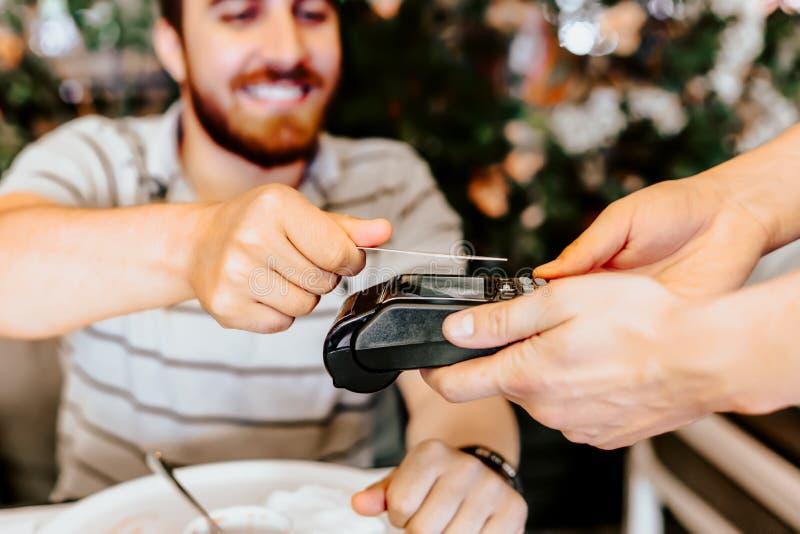 Chiuda sui dettagli dell'uomo che pagano con la carta di credito al ristorante fotografie stock