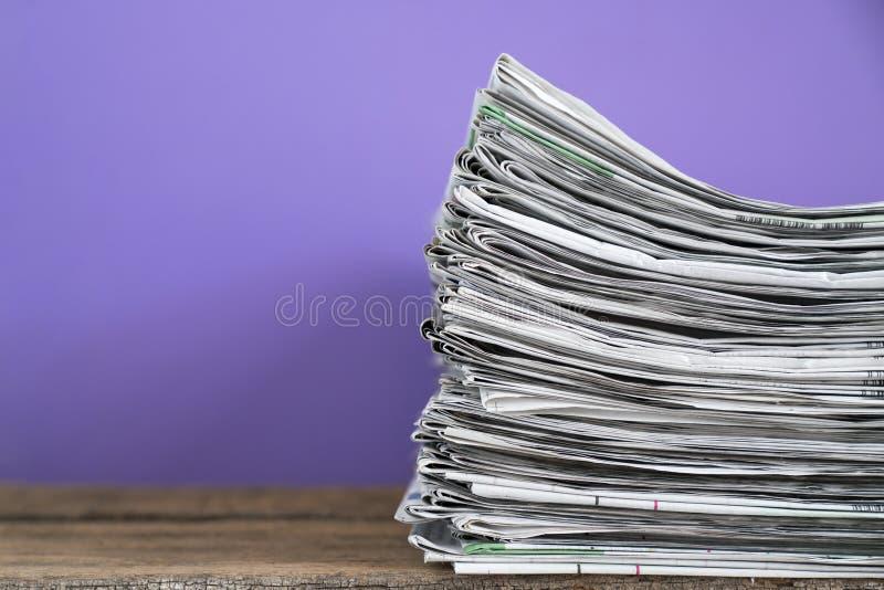 Chiuda sui giornali piegati e sul fondo impilato sulla tavola immagini stock libere da diritti
