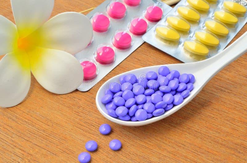 Chiuda sui molti la compressa porpora della medicina sul cucchiaio con la compressa nel pacchetto, in fiore bianco e nel ramo di  immagini stock