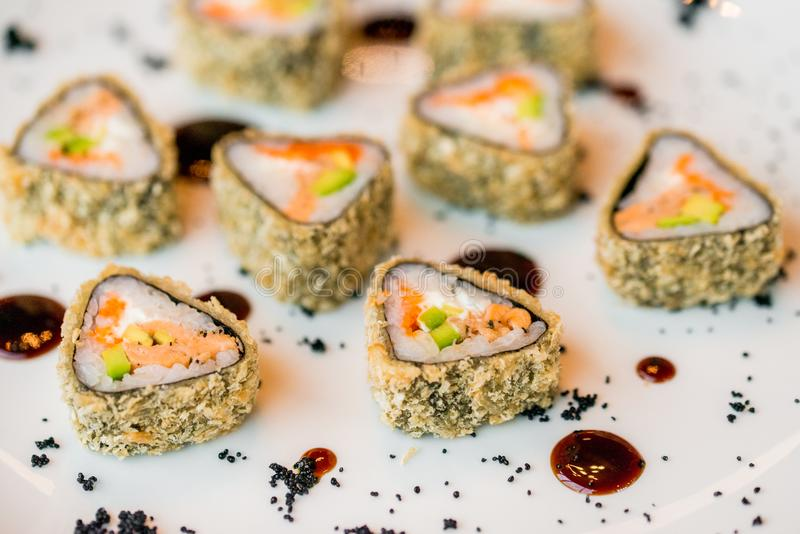 Chiuda sui rotoli di sushi deliziosi del triangolo sul piatto fotografie stock libere da diritti
