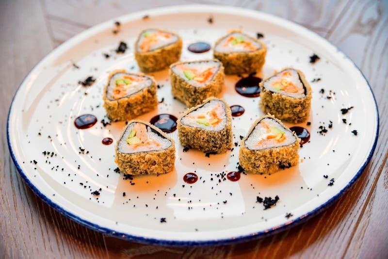 Chiuda sui rotoli di sushi deliziosi del triangolo sul piatto fotografia stock