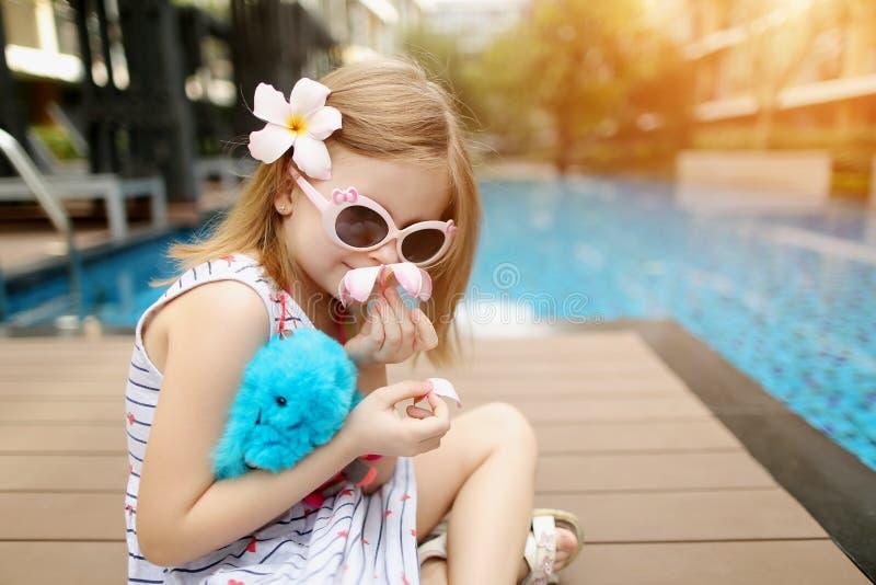 Chiuda sul bambino che si siede vicino agli occhiali da sole d'uso della piscina il giorno soleggiato immagini stock