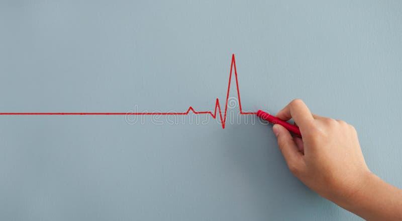 Chiuda sul battito cardiaco del disegno della donna con gesso rosso sulla parete immagini stock