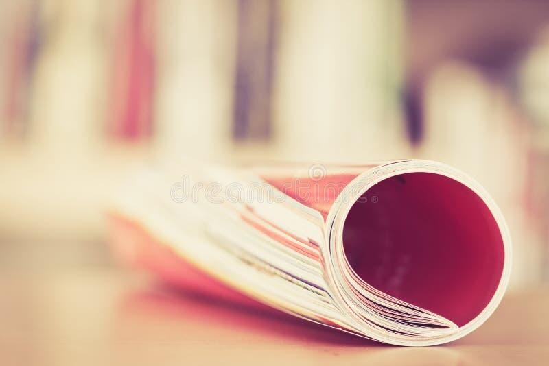 Chiuda sul bordo della rivista variopinta che impila il rotolo con la BO confusa immagini stock