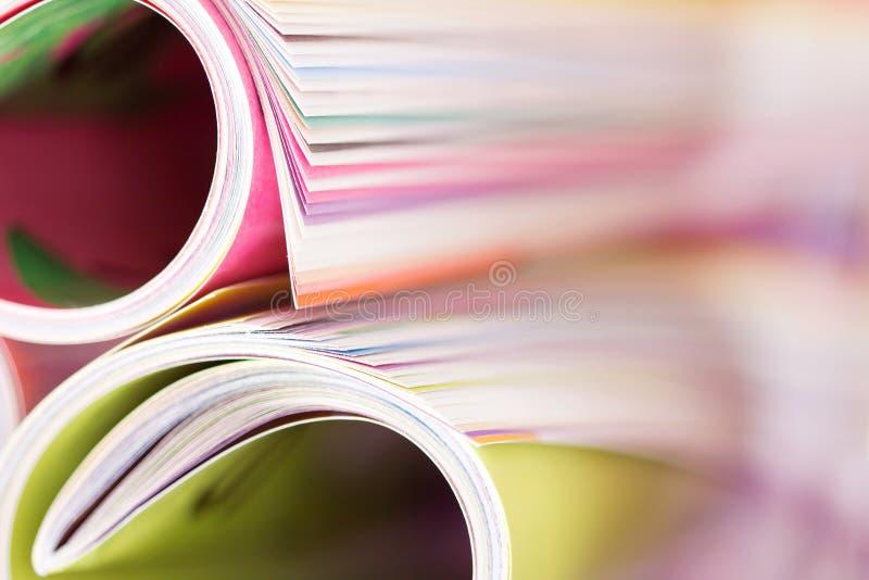 Chiuda sul bordo della rivista variopinta che impila il rotolo con la BO confusa immagine stock libera da diritti