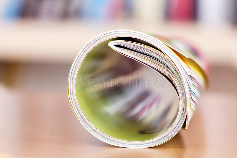 Chiuda sul bordo della rivista variopinta che impila il rotolo con la BO confusa fotografia stock