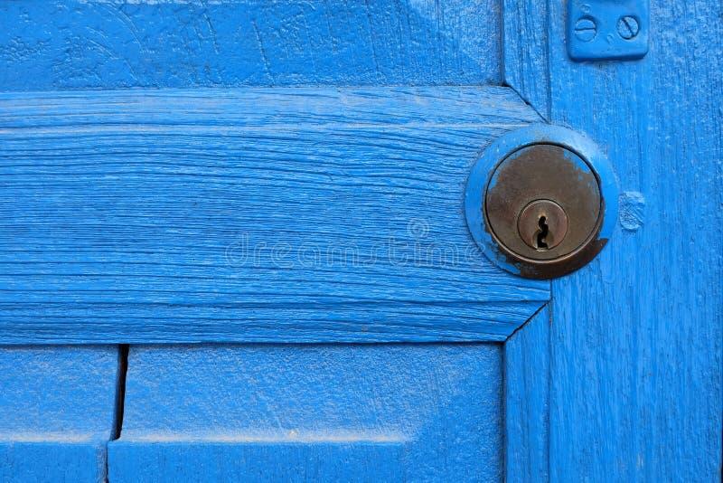 Chiuda sul buco della serratura con la porta blu di legno fotografia stock