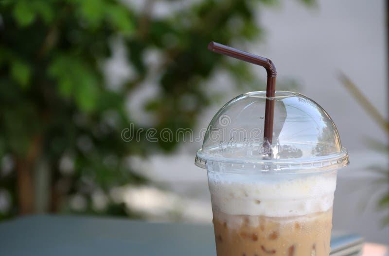 Chiuda sul caffè di ghiaccio nella tazza di plastica con paglia marrone e fuori metta a fuoco il taccuino fotografia stock