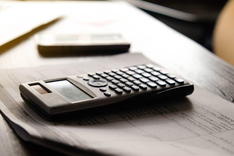 Chiuda sul calcolatore che conta facendo le note a casa, il conto ed il concetto finanziario fotografia stock
