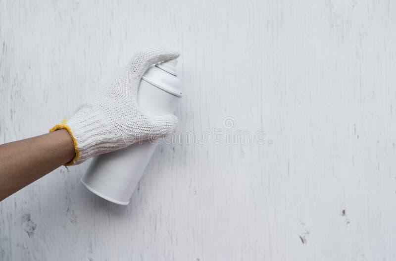 Chiuda sul carpentiere nella sua stanza della pittura che spruzza un pezzo di legno da utilizzare pi? successivamente nella sua o fotografia stock libera da diritti