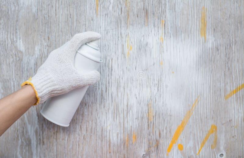 Chiuda sul carpentiere nella sua stanza della pittura che spruzza un pezzo di legno da utilizzare pi? successivamente nella sua o fotografia stock