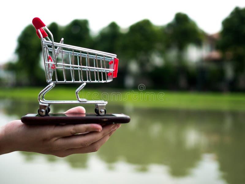 Chiuda sul carrello sul telefono cellulare, affare nel concetto di commercio elettronico fotografia stock