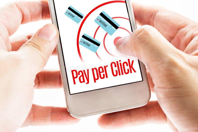 Chiuda sul cellulare della tenuta di due mani con paga per parola di clic, Digita immagine stock
