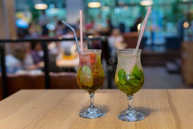 Chiuda sul cocktail con ghiaccio in vetro e paglia Cocktail freddo fresco di mojito su una tavola di legno immagini stock libere da diritti