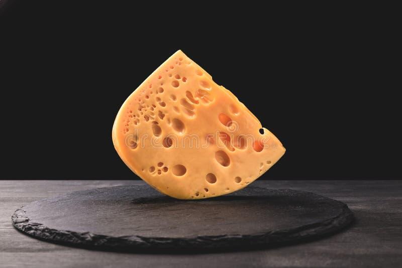 Chiuda sul colpo del formaggio dell'emmental a bordo sul nero immagine stock