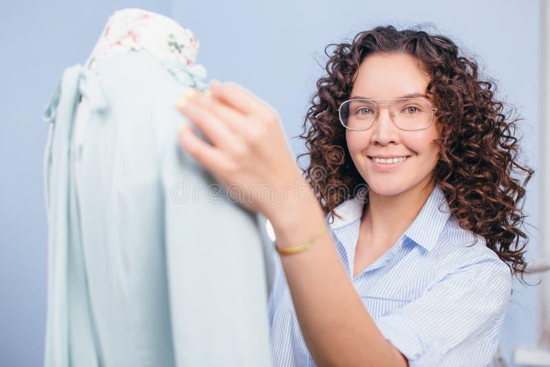 Chiuda sul colpo della cucitrice che regola il vestito sul manichino al negozio del sarto fotografia stock