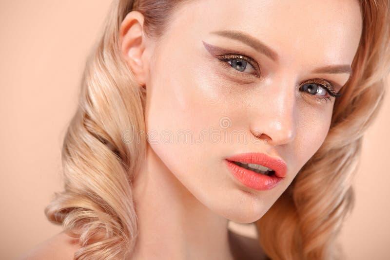 Chiuda sul colpo della femmina caucasica affascinante con capelli biondi, esaminante delicatamente la macchina fotografica Tenero fotografie stock
