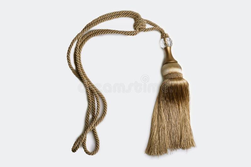 Chiuda sul colpo di un nodo decorativo della nappa con una corda intrecciata dentro fotografie stock libere da diritti