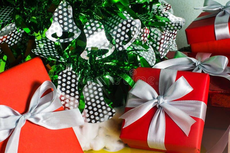Chiuda sul contenitore di regalo rosso e bianco sulla tavola di legno con il fondo della pigna e del pino immagine stock