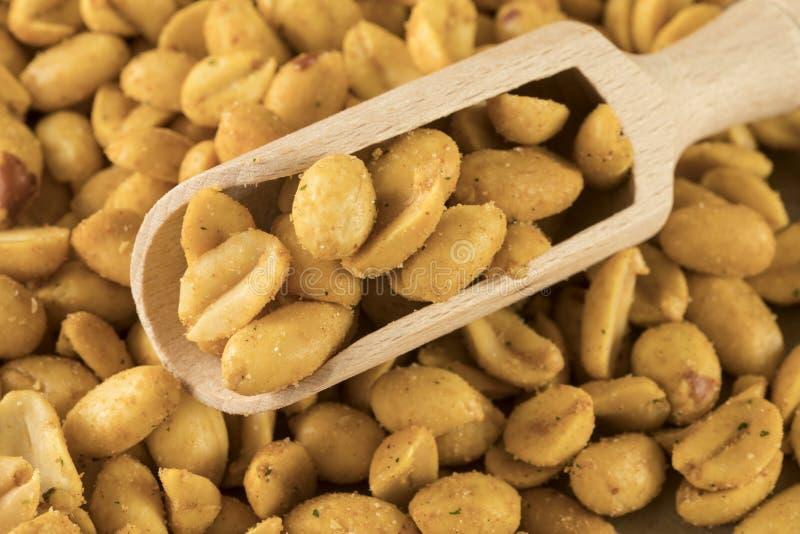 Chiuda sul cucchiaio di legno in arachidi del mucchio immagine stock libera da diritti