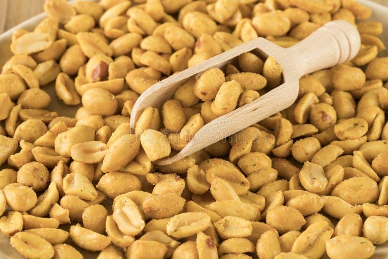 Chiuda sul cucchiaio di legno in arachidi del mucchio fotografia stock