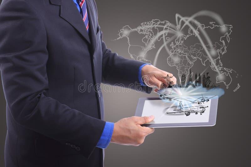 Chiuda sul cuscinetto di tocco di uso dell'uomo d'affari per il concetto di viaggio fotografia stock