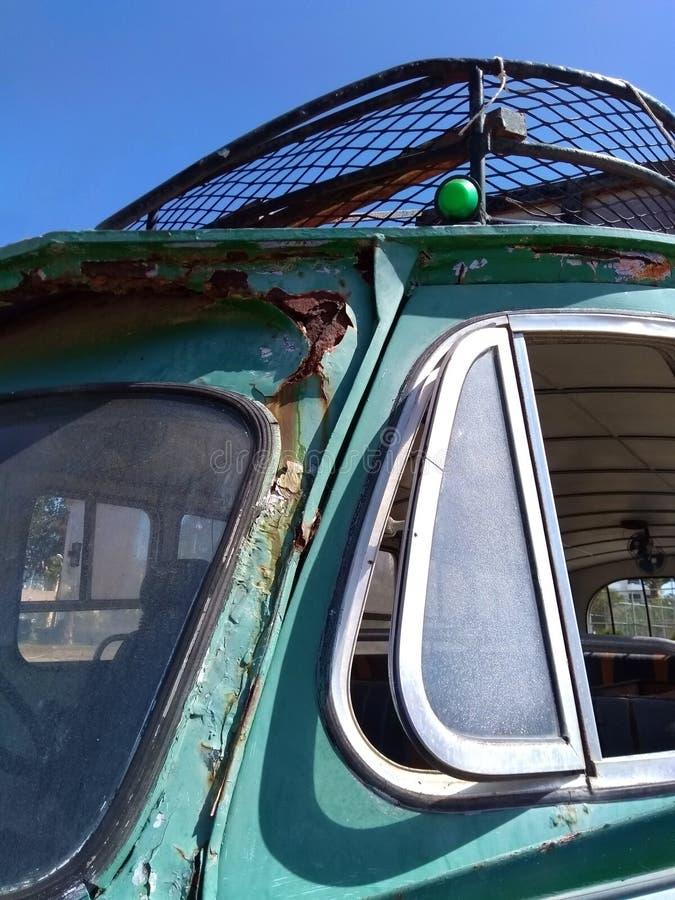 Chiuda sul dettaglio del tergicristallo e delle finestre laterali di vecchio bus verde abbandonato arrugginito fotografie stock