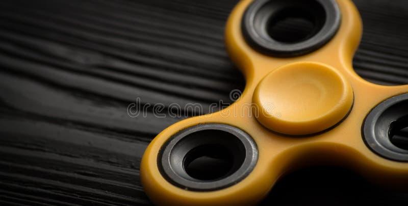 chiuda sul filatore giallo su un fondo nero immagine stock